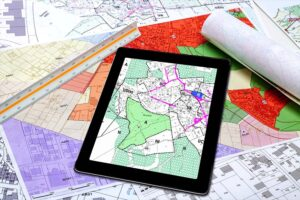 tablet with a map on it on top of paper maps